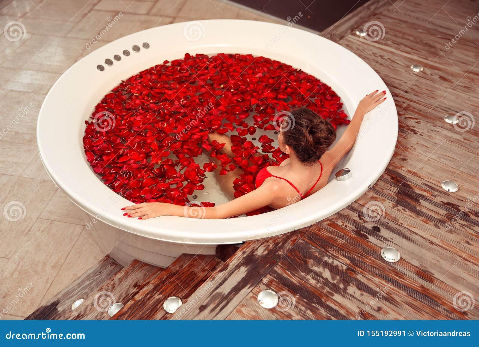 Het kuuroord ontspant Mooi meisje in Jacuzzi Bikinivrouw die in rond bad met rode roze bloemblaadjes liggen Gezondheid en schoonh