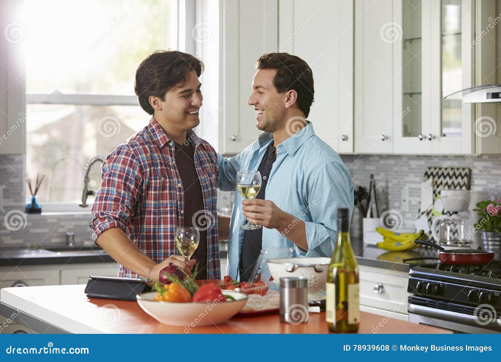 Het lachen mannelijke vrolijke paar het drinken wijn en het voorbereiden van een maaltijd