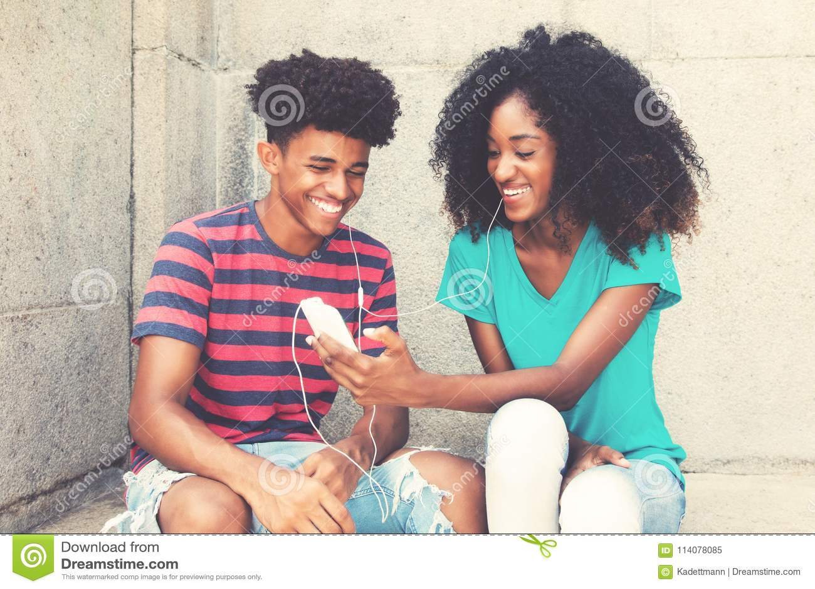 Het lachende Afrikaanse Amerikaanse jonge volwassen paar houdt van muziek