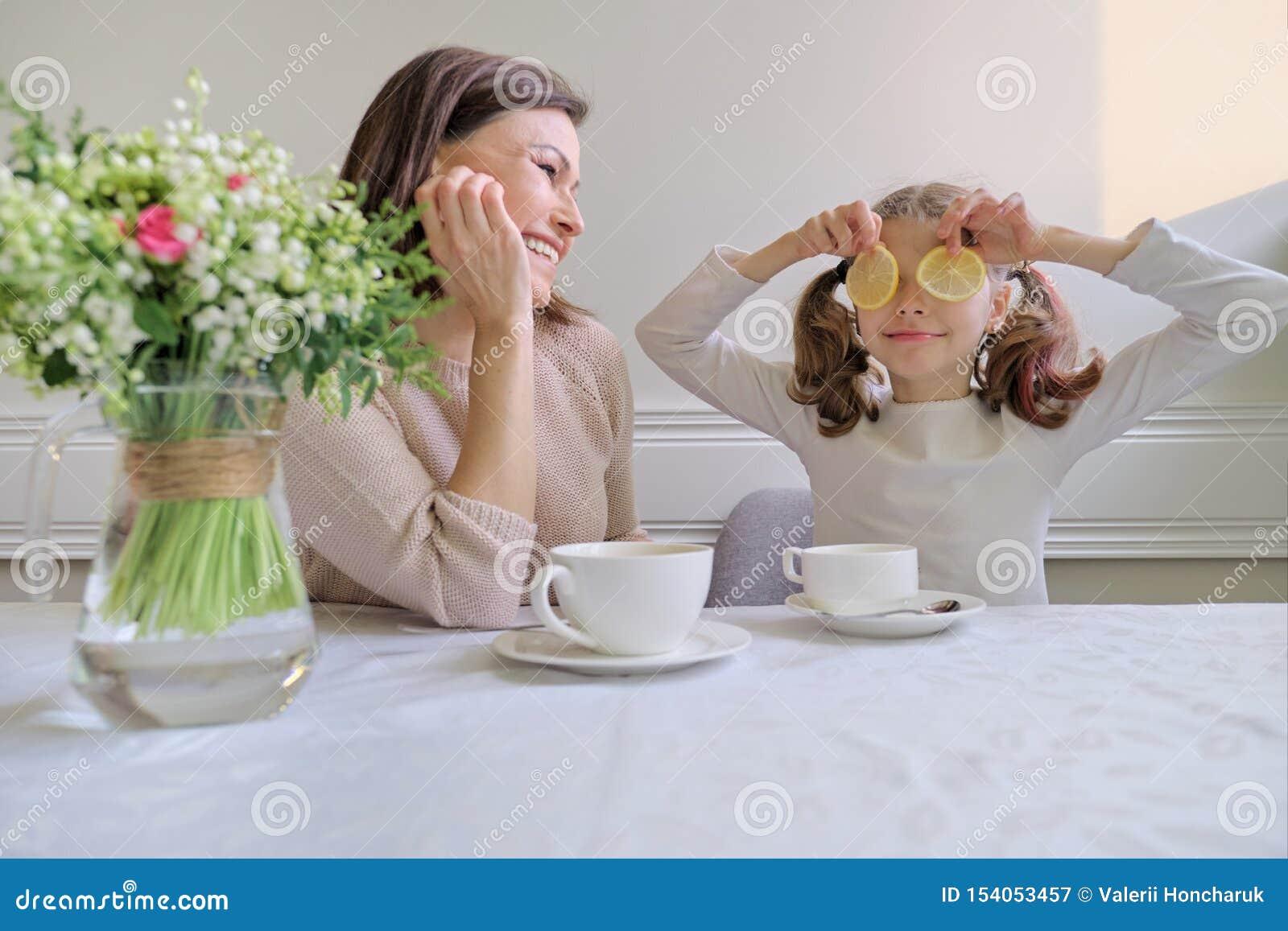 Het lachende moeder en dochter drinken van koppen en het eten van citroen