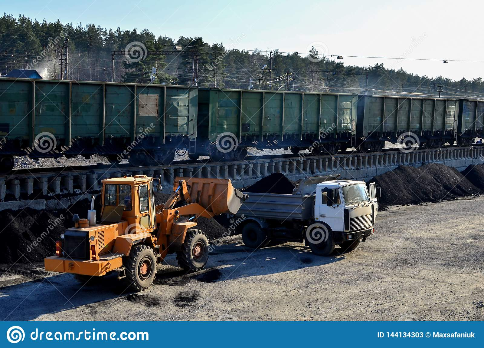 Het ladergraafwerktuig laadt steenkool in een stortplaatsvrachtwagen bij een ladingsstation