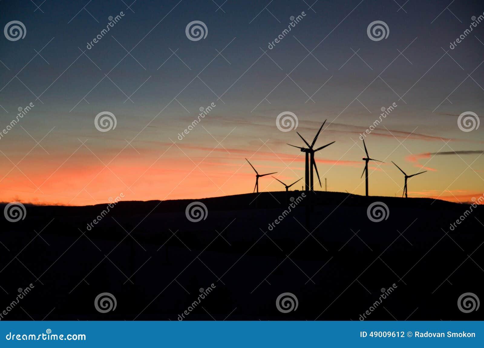 Het landbouwbedrijf van de windturbine bij zonsondergang