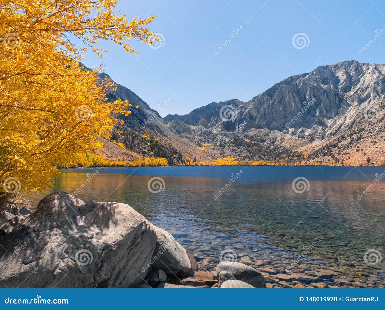 Het landschap van het bergmeer met overweldigende de herfstkleuren en blauw water