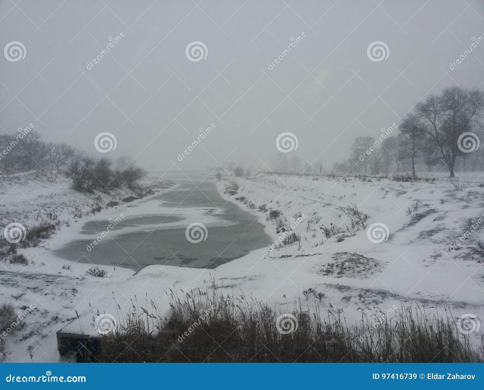 Het landschap van de winter Een kleine rivier onder een de wintersneeuwstorm Prentbriefkaar met een rivier in de winter Lage temp