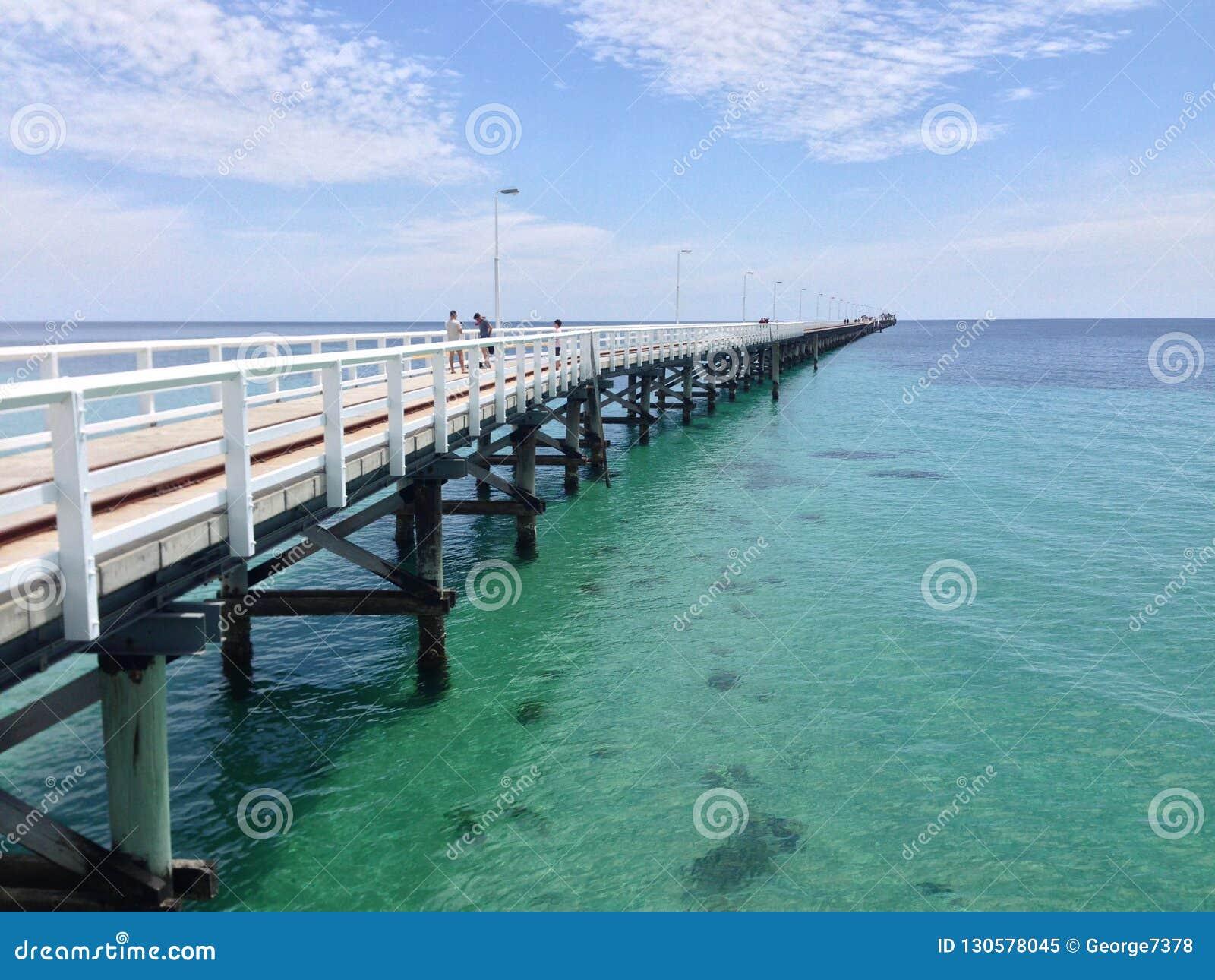 Het lange houten pier uitrekken zich over oceaan