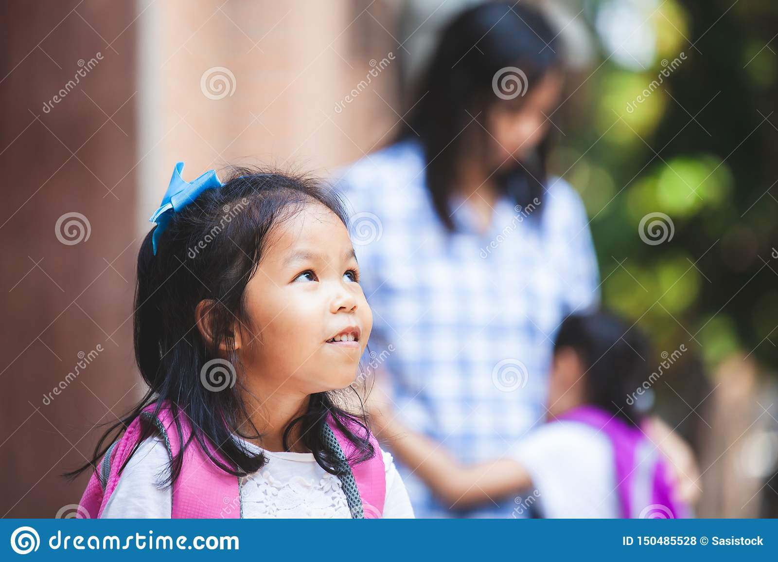 Het leuke Aziatische kindmeisje die haar zuster wachten gaat samen naar school na omhelzing hun moeder