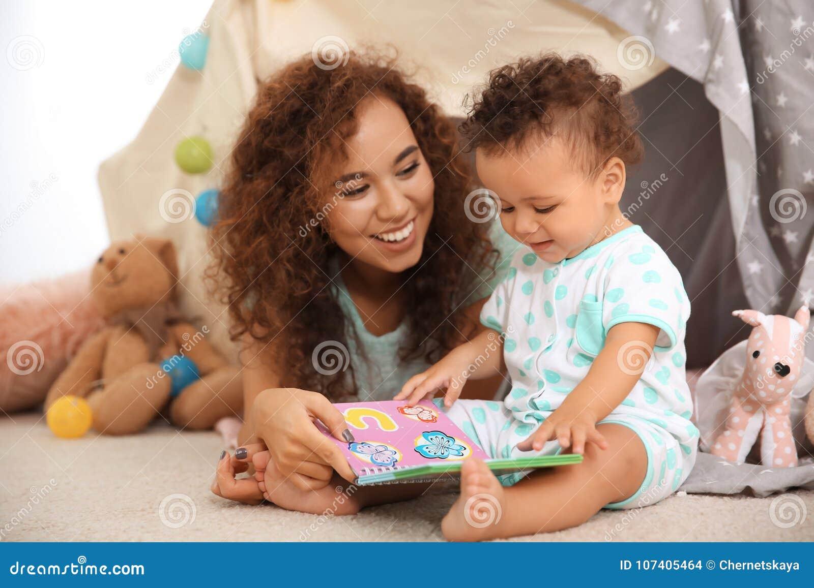 Het leuke baby en moeder spelen op vloer