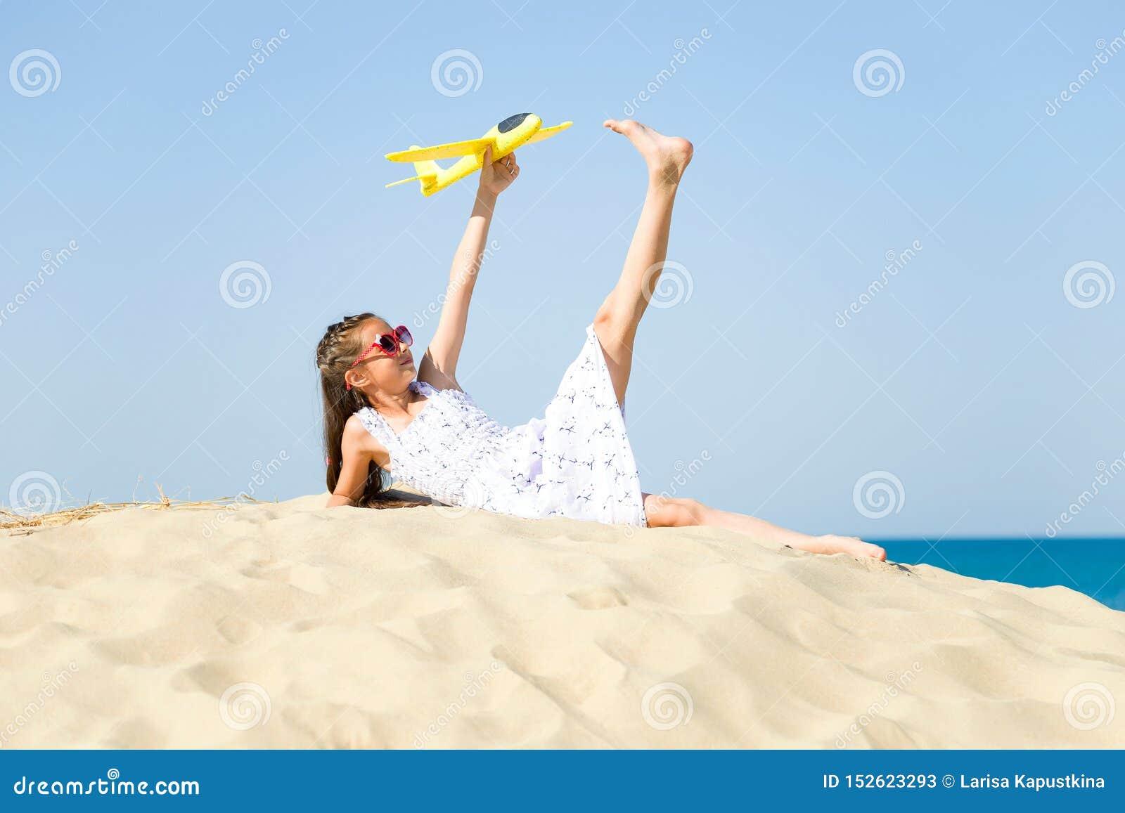 Het leuke gelukkige meisje zonoogglazen dragen en een wit die kleden het liggen op het zandige strand door het overzees en playi