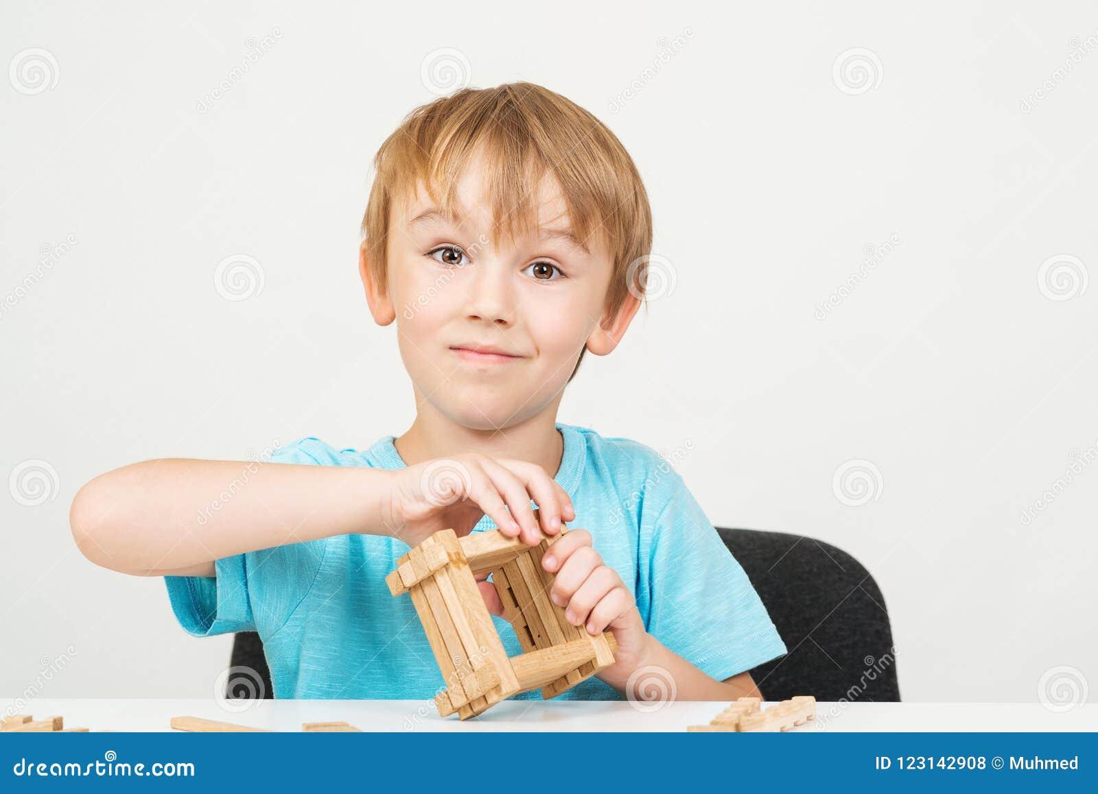 Het leuke jongen spelen met houten die blokken, op witte achtergrond worden geïsoleerd Onderwijs Het schot van de studio Terug na