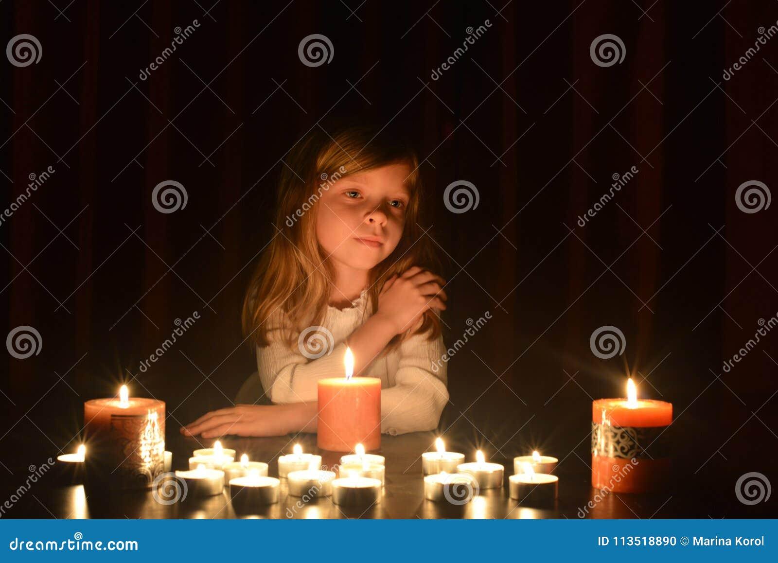 Het leuke kleine blondemeisje houdt haar hand op haar schouder en zij bekijkt de brandende kaars Veel kaarsen zijn rond h