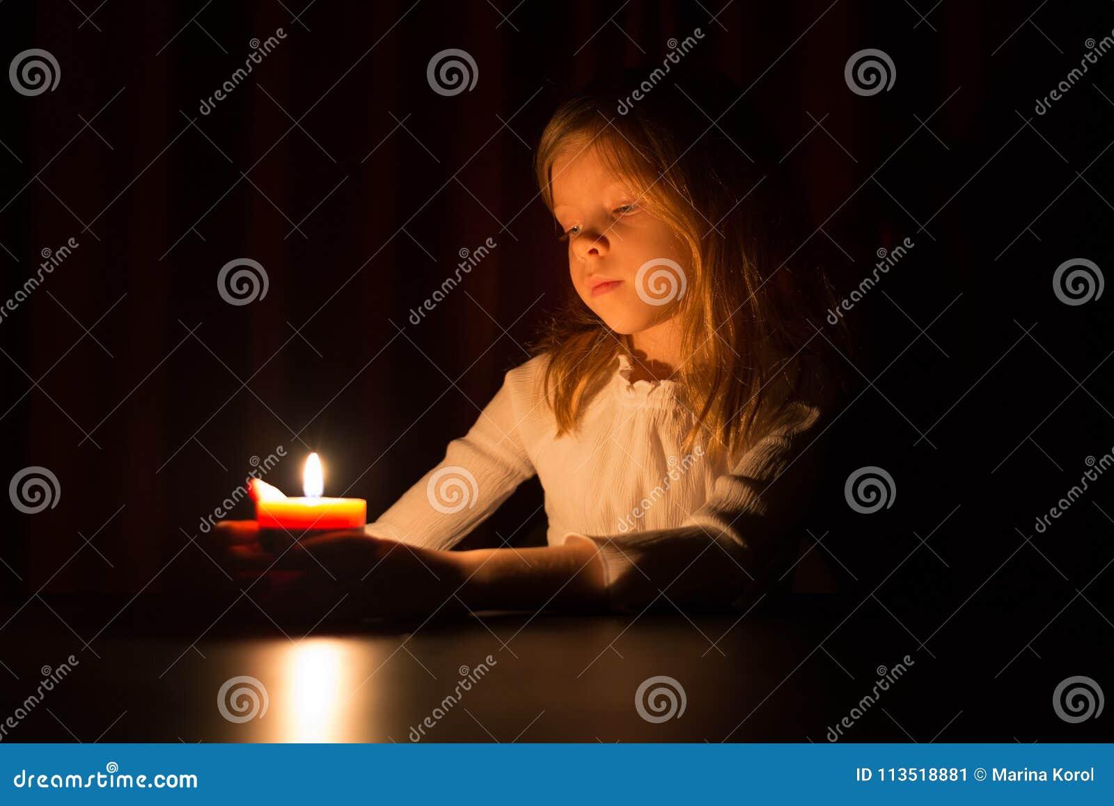 Het leuke kleine blondemeisje kijkt op het licht van kaars over donkere achtergrond