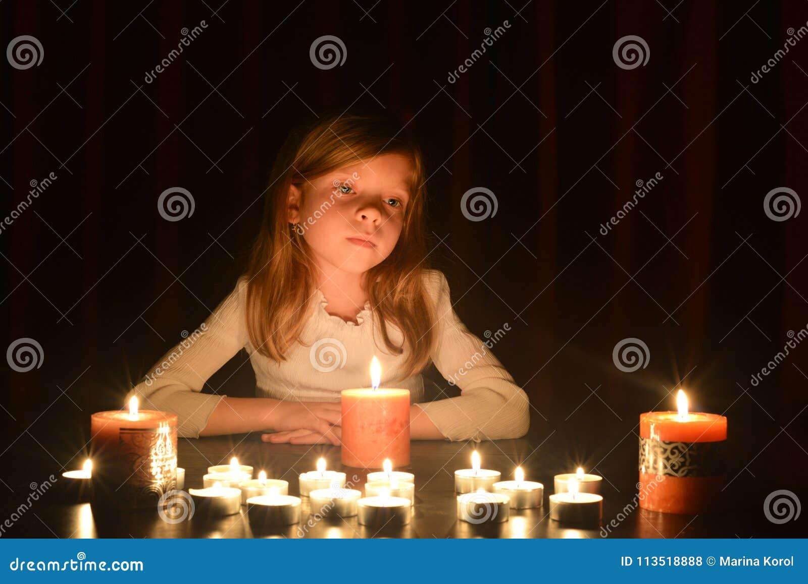 Het leuke kleine blondemeisje kijkt op het licht van kaars Veel kaarsen zijn rond haar, over donkere achtergrond