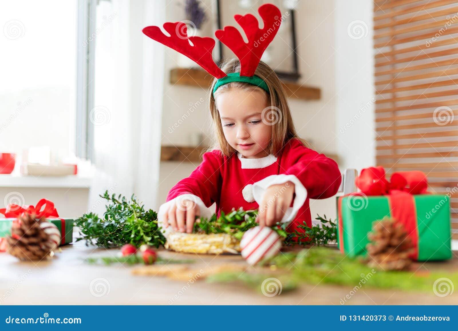 Het leuke kleutermeisje kleedde zich in rendierkostuum die rendiergeweitakken dragen makend Kerstmiskroon in woonkamer