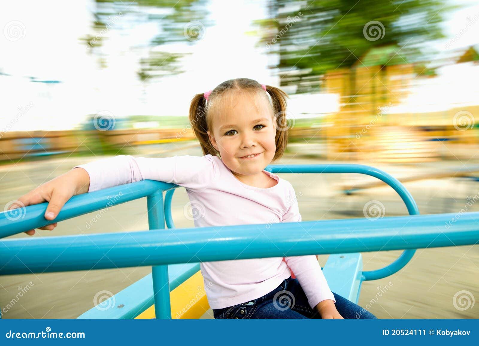 Het leuke meisje berijdt op vrolijk-gaan-rond