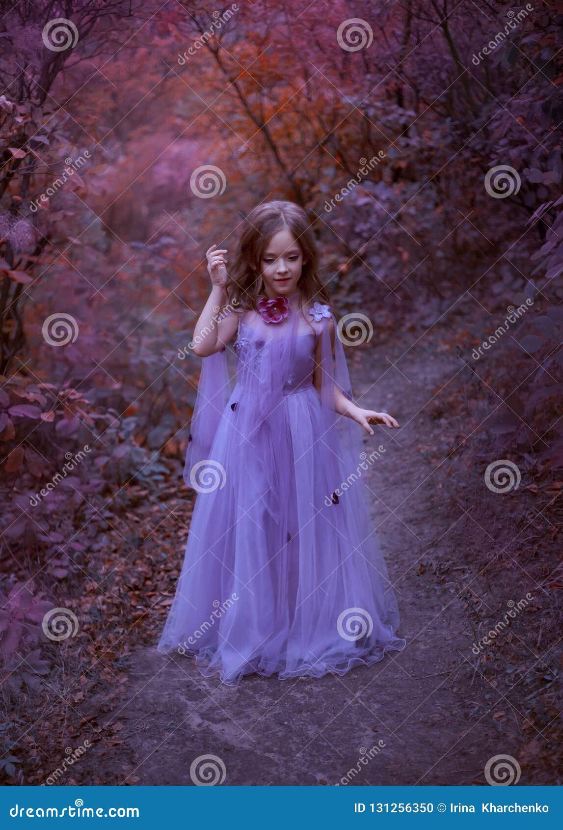 Het leuke meisje bevindt zich in het bos in een purpere lichte lange kleding met bloemen, een kleine prinses als in een droom, ga