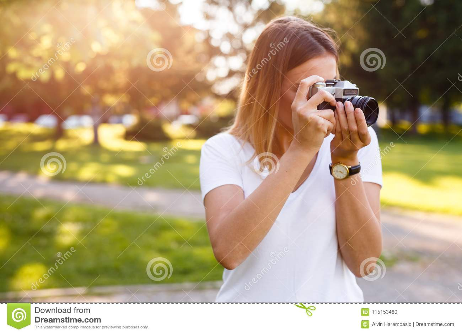 Het leuke meisje op zonnige dag in parkeren die foto s met analogon nemen kwam