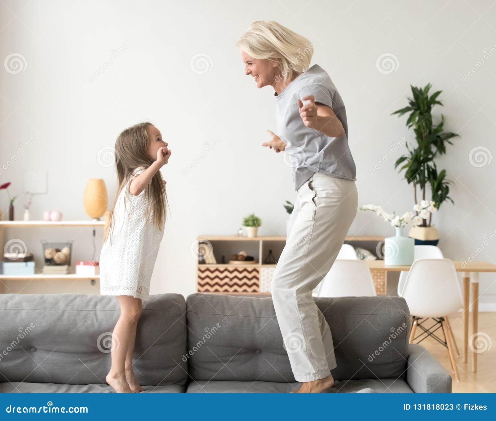 Het leuke meisje spelen met grootmoeder het springen op laag toget