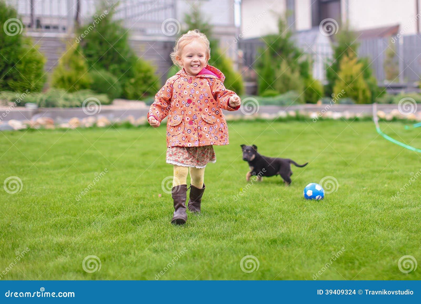Het leuke meisje spelen met haar puppy in de werf
