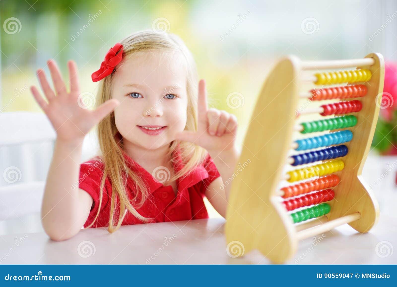 Het leuke meisje spelen met telraam thuis Slim kind die leren te tellen
