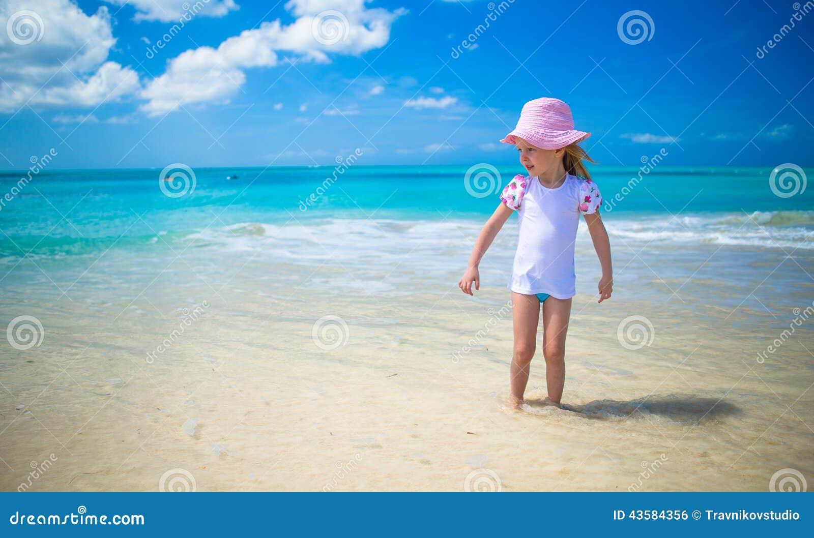 Het leuke meisje spelen in ondiep water bij