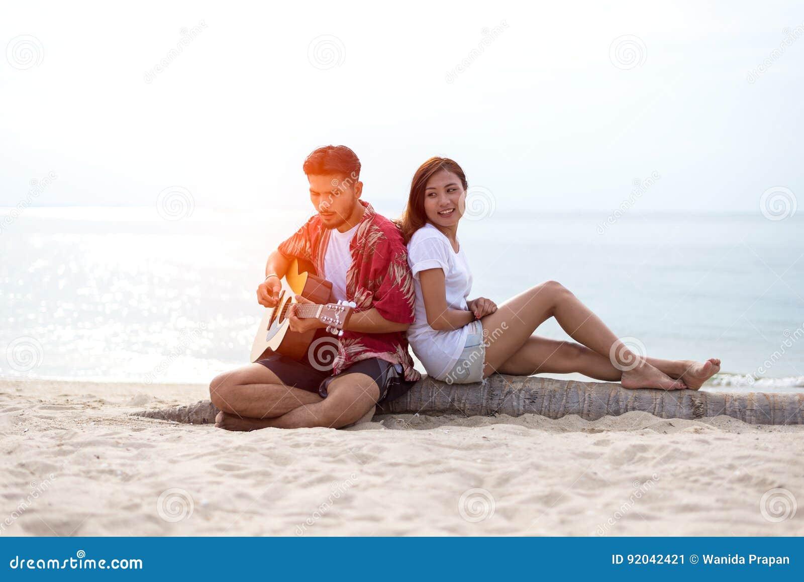 Het leuke Spaanse paar speelgitaar serenading op strand