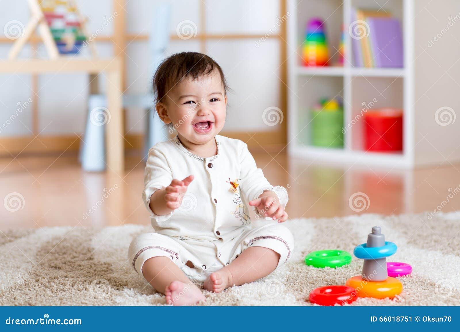 Het leuke vrolijke baby spelen met kleurrijk stuk speelgoed thuis