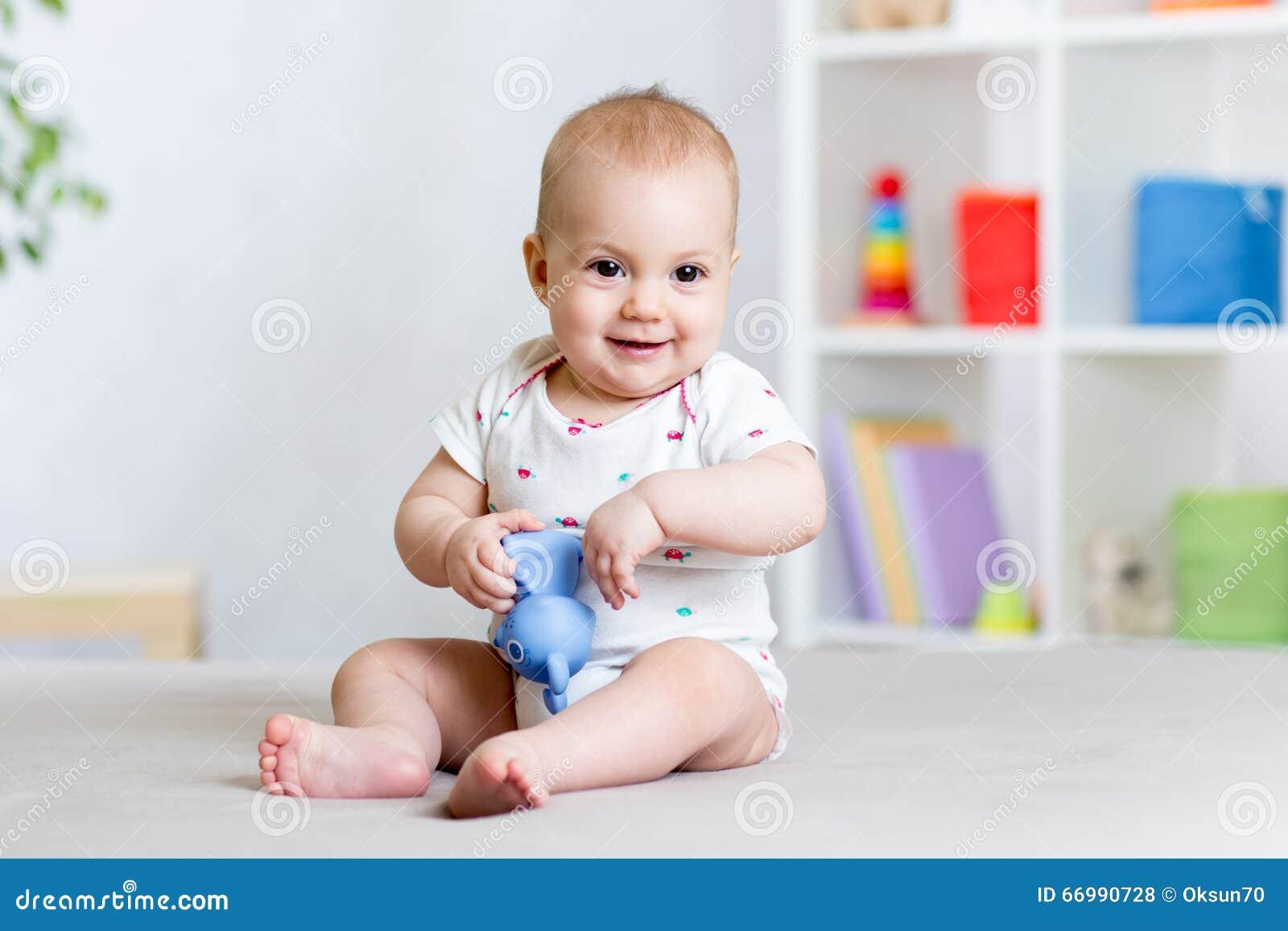 Het leuke vrolijke baby spelen met stuk speelgoed thuis