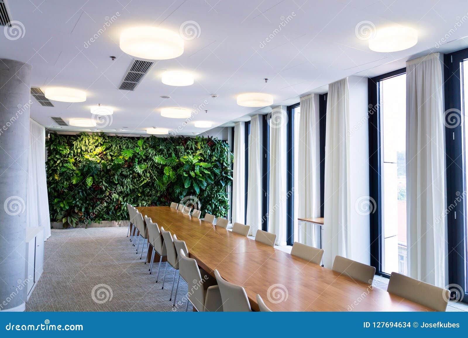 Het leven groene muur, verticale tuin binnen met bloemen en installaties onder kunstmatige verlichting in vergaderingsbestuurskam