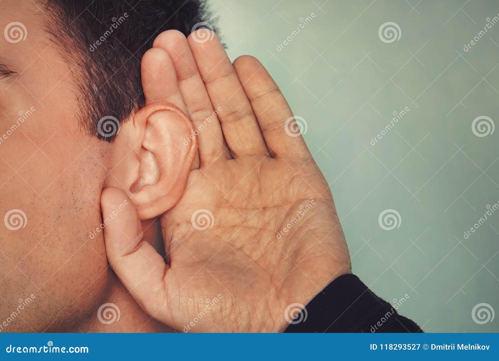 Het luistermannetje houdt zijn hand dichtbij zijn oor concept doofheid of het afluisteren Hard van Hoorzitting