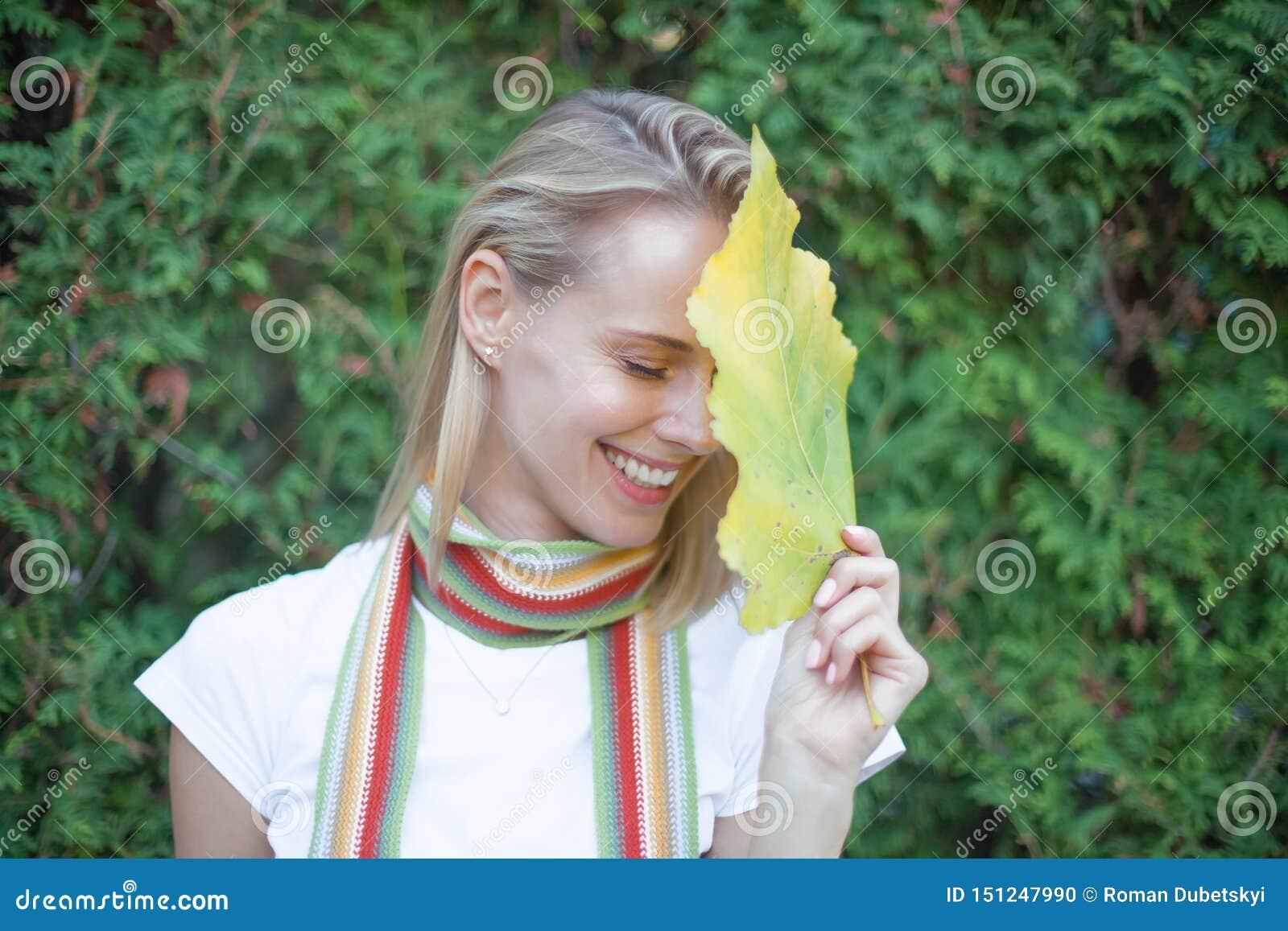Het luxeportret van een Mooie jonge vrouw met natuurlijke make-up houdt een groot groen blad op een vage groene achtergrond KUURO