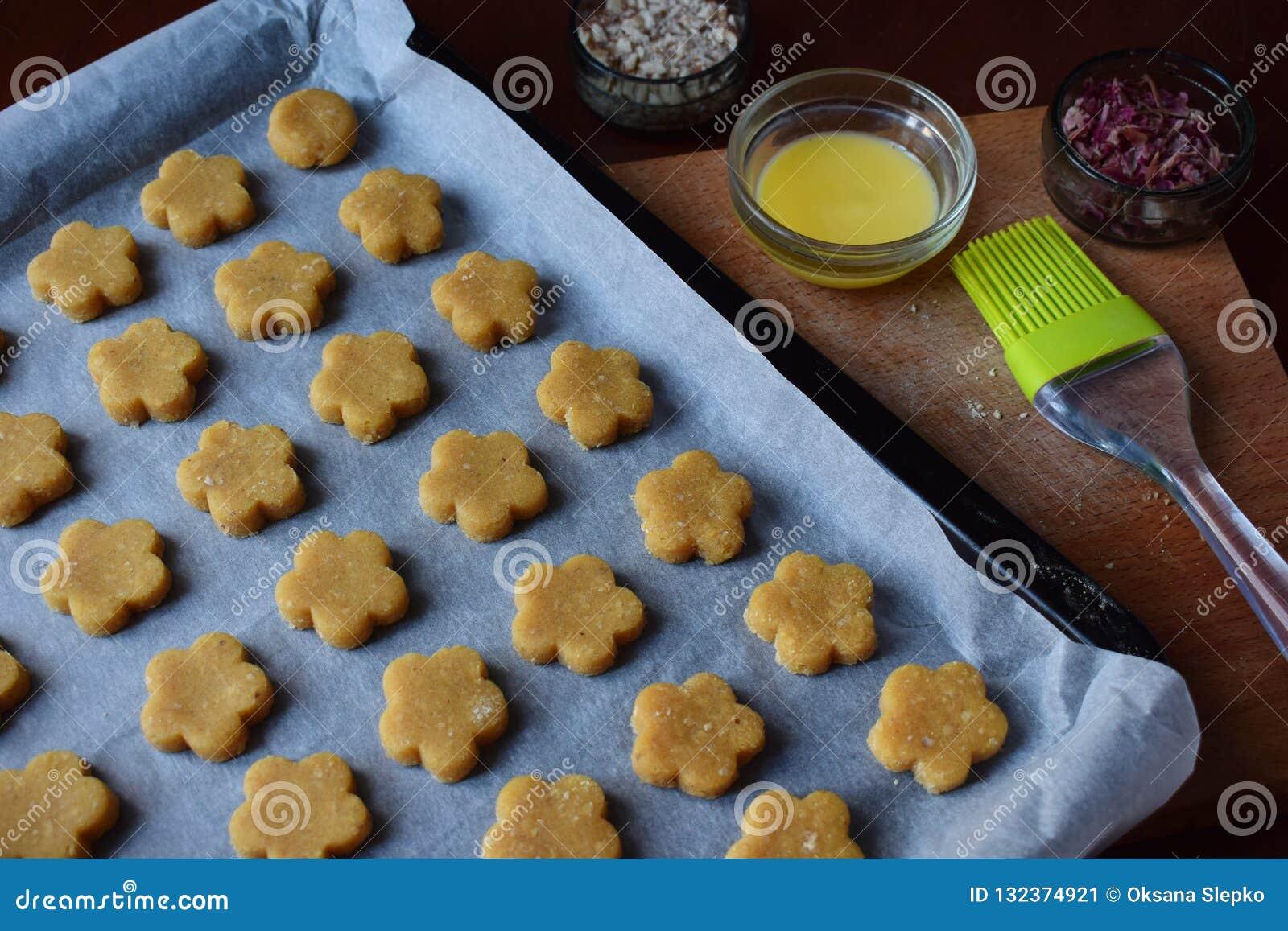 Het maken van de gebakjes van kikkererwtenkoekjes met amandelen en thee nam bloemblaadjes toe Traditionele Oostelijke snoepjes Vr