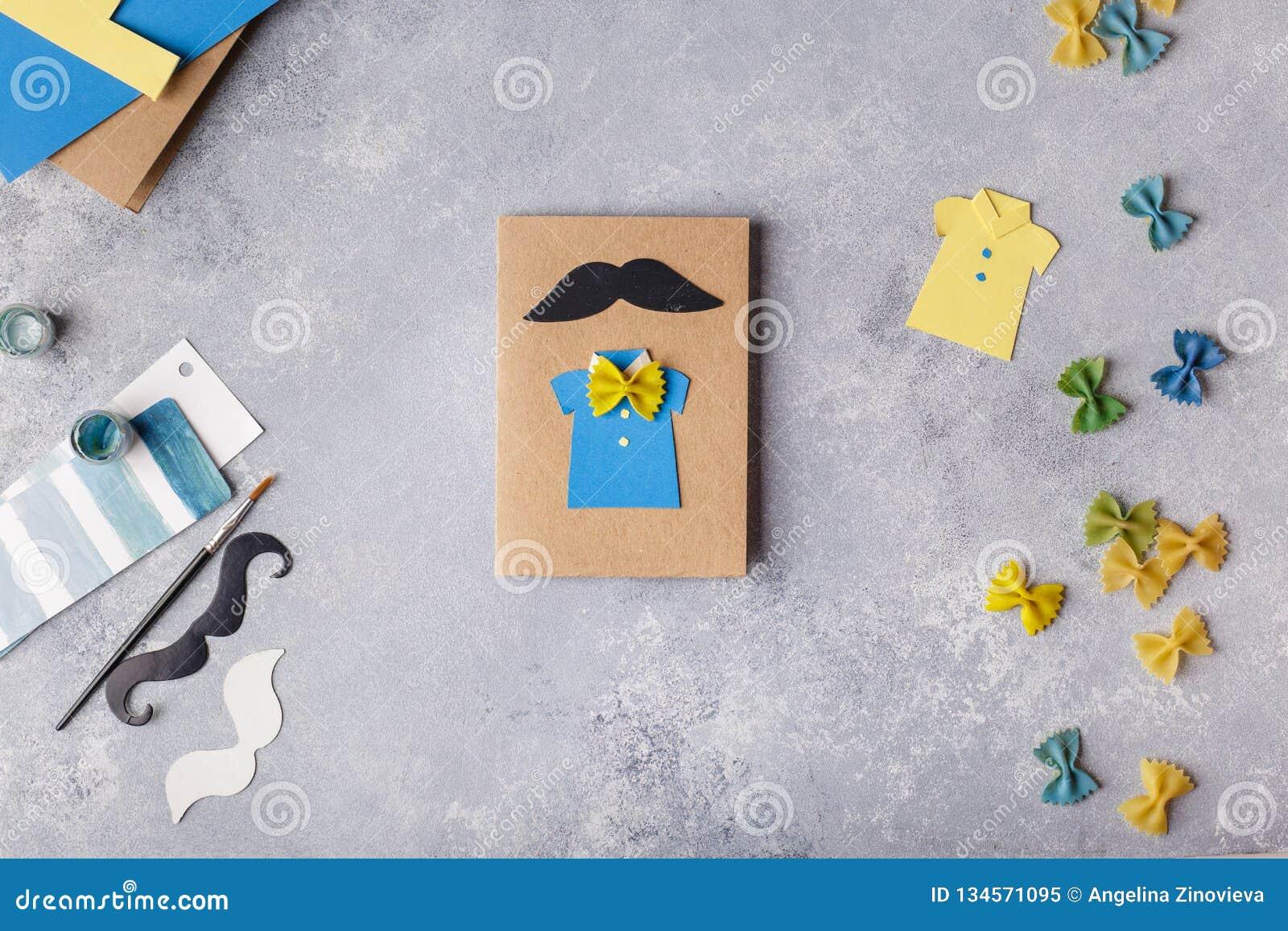 Het maken van groetkaart voor Vadersdag Overhemd met vlinder van deegwaren Kaart van document moustache De kunstproject van kinde
