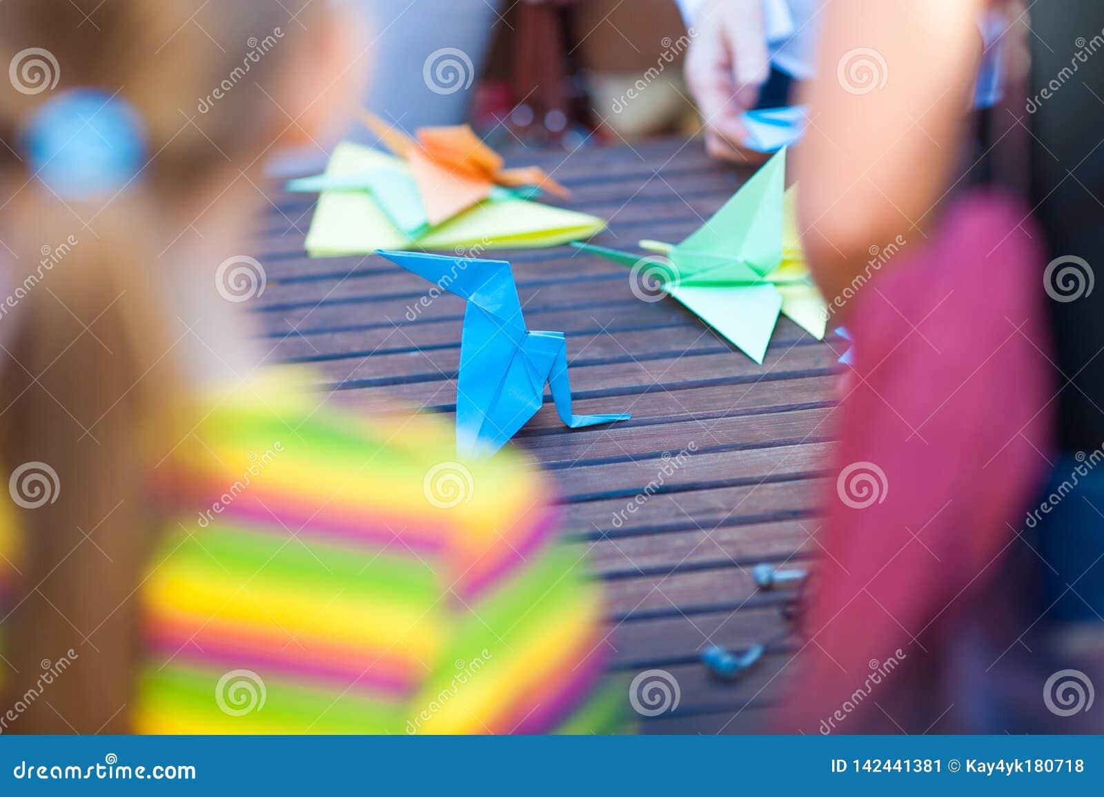 Het maken van origami, die met gekleurd document, kinderenvorm van document werken