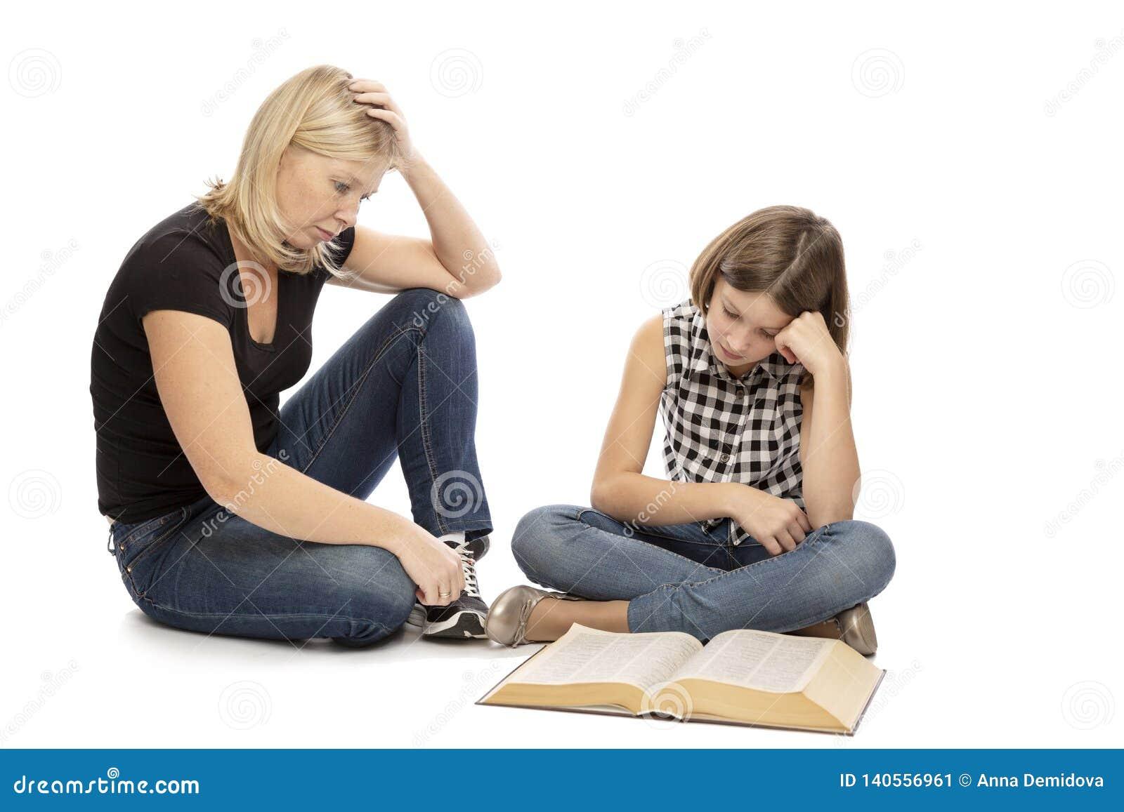 Het mamma helpt haar tienerdochter die lessen te leren, op witte achtergrond worden geïsoleerd
