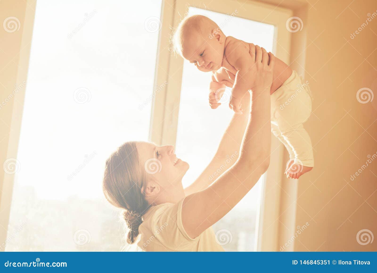 Het mamma hief de baby in haar wapens boven haar hoofd op