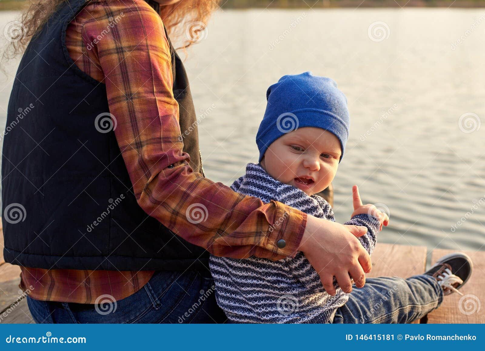Het mamma koestert haar zoon op de pijler op de rivier