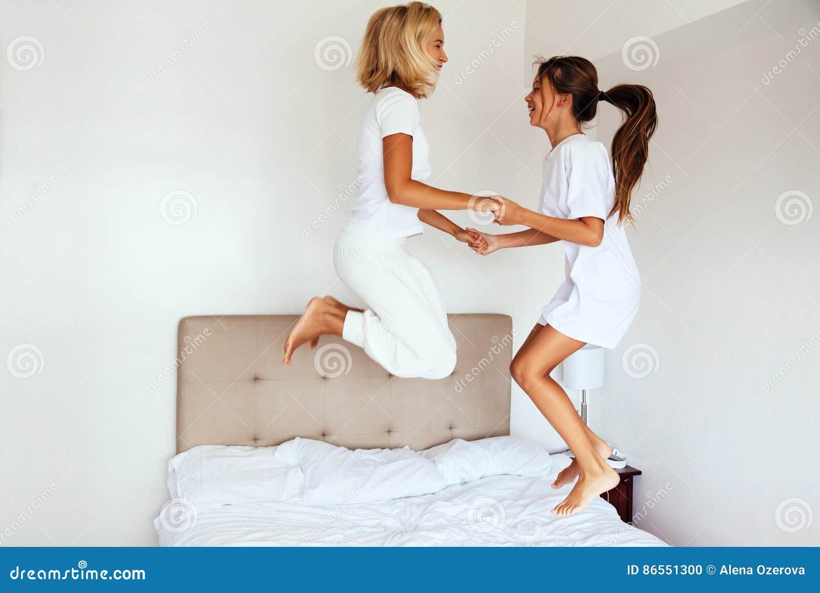 Het mamma met haar preteen kind het springen op bed