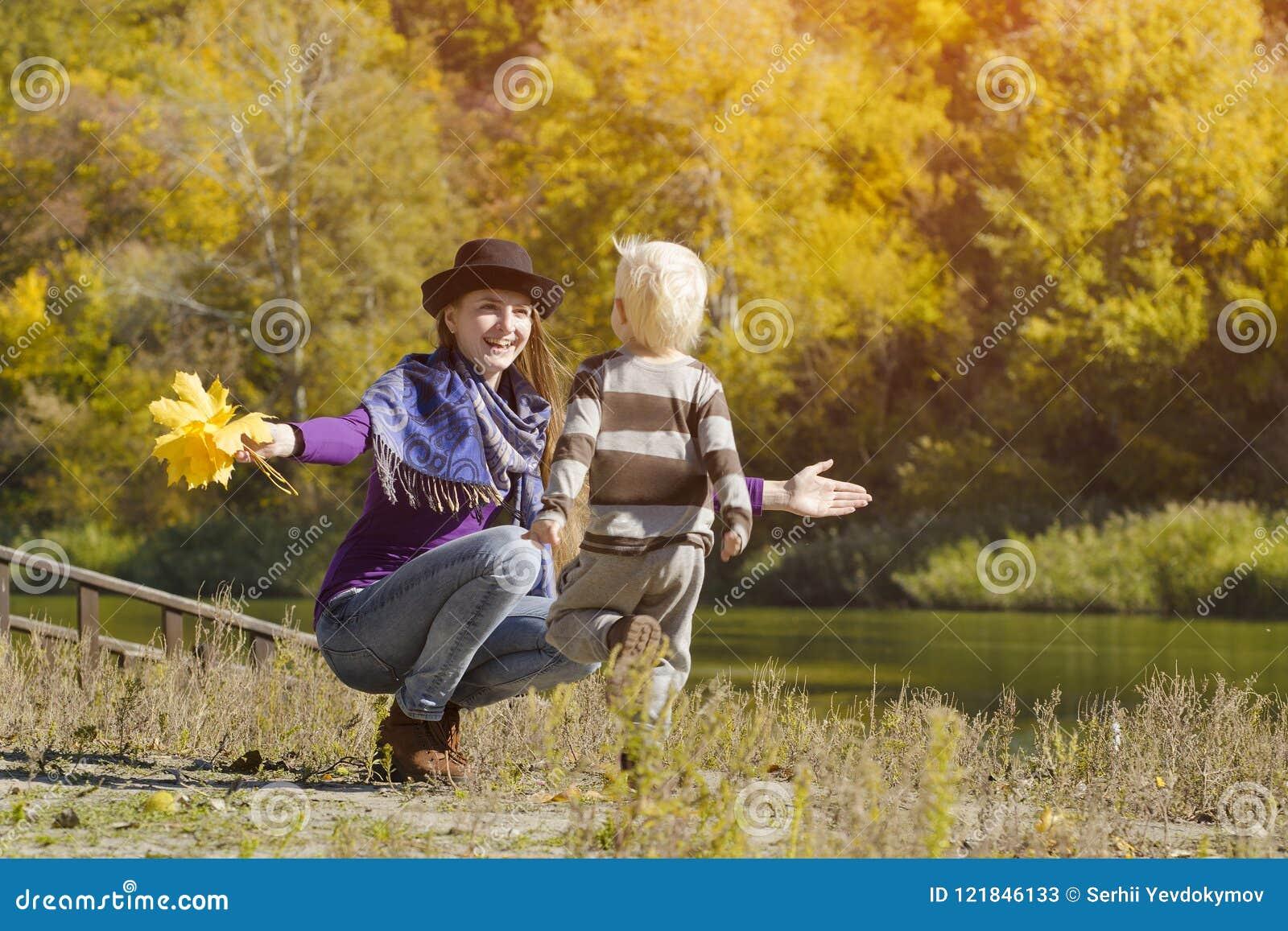 Het mamma vangt lopende zoon De herfst, een zonnige dag Rivierbank