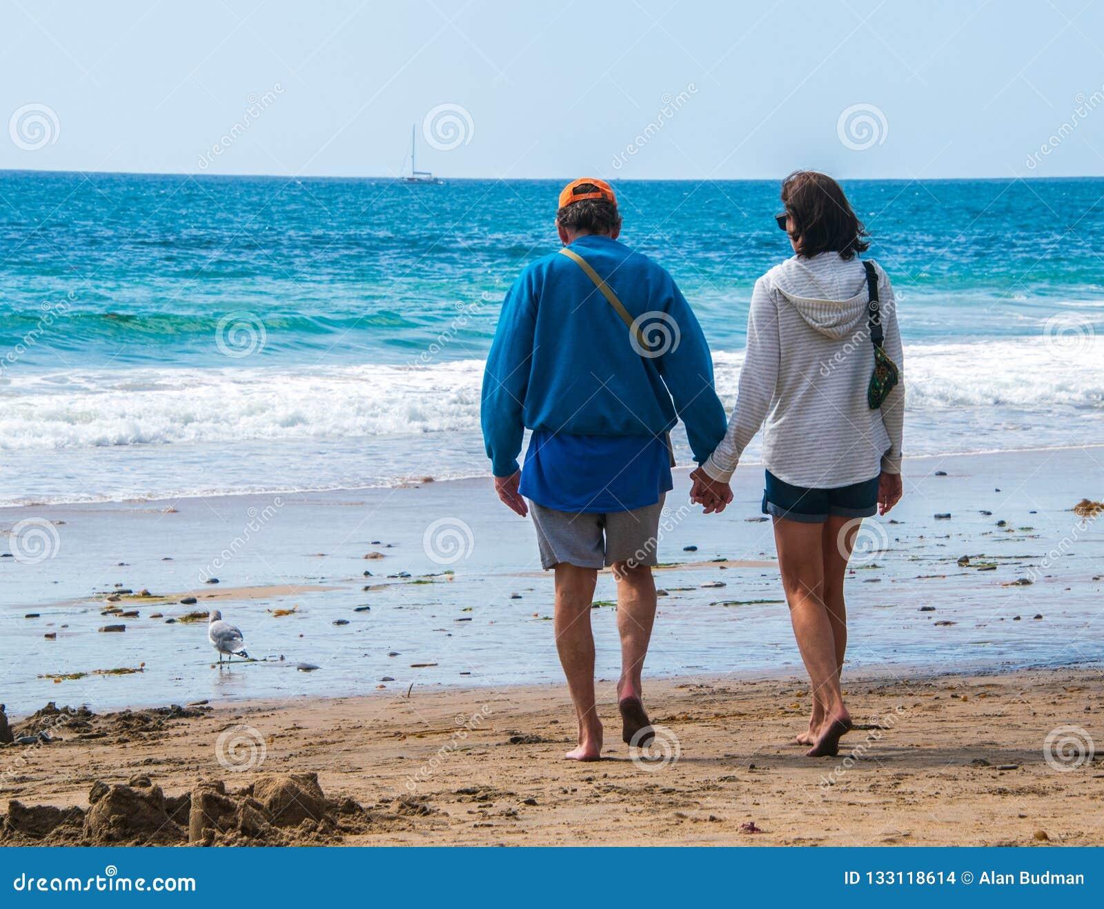 Het mannelijke en vrouwelijke Kaukasische paar die van de bejaardebaby boomer op het strand naar de oceaanholdingshanden lopen