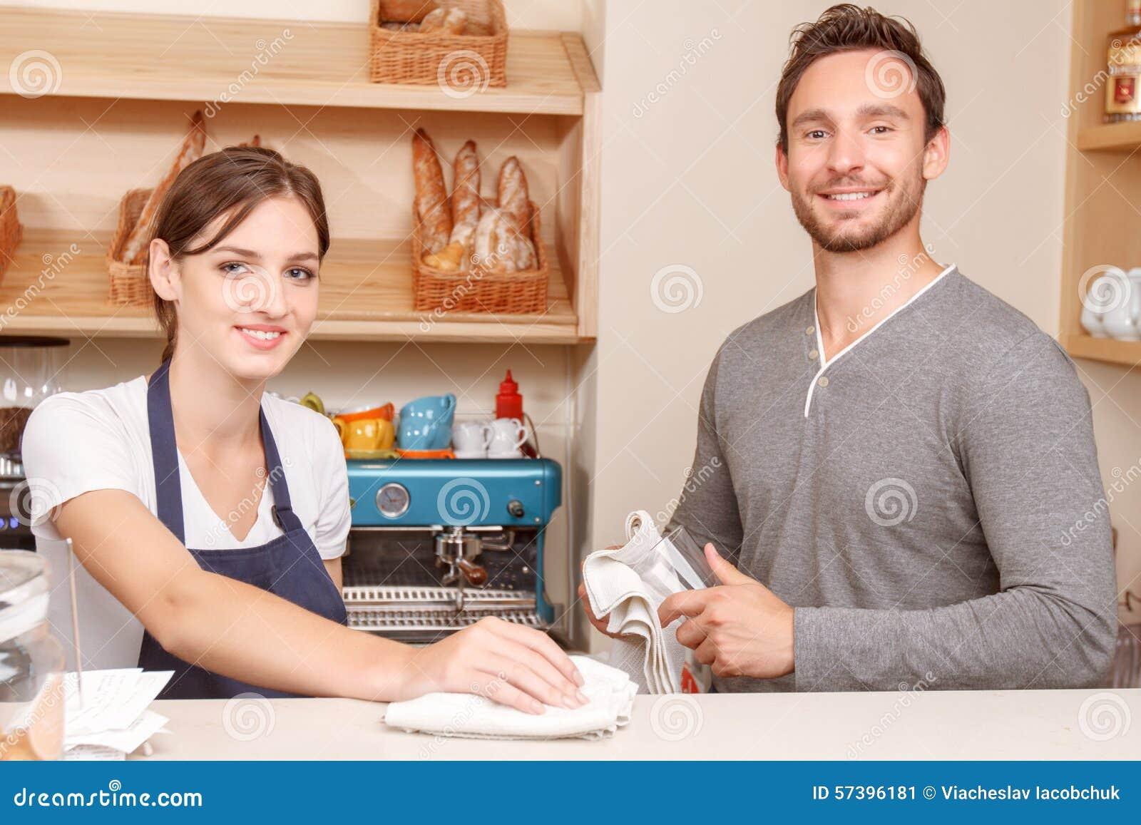 Het mannelijke en vrouwelijke koffiearbeiders schoonmaken