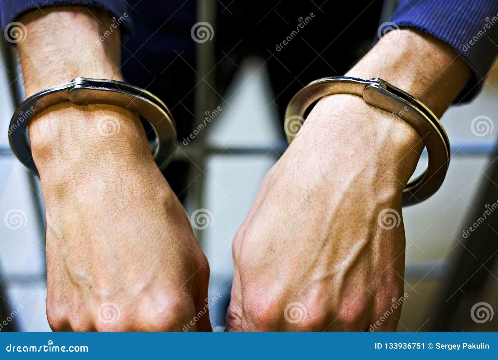 Het mannetje dient metaalhandcuffs close-up in Een gevangene in gevangenis het concept straf voor een misdaad
