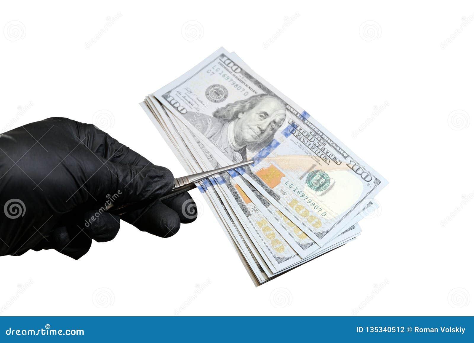 Het mannetje dient zwarte handschoen in houdt een pak Amerikaanse dollars met pincet Voorwerp voor het ontwerp van het concept sc