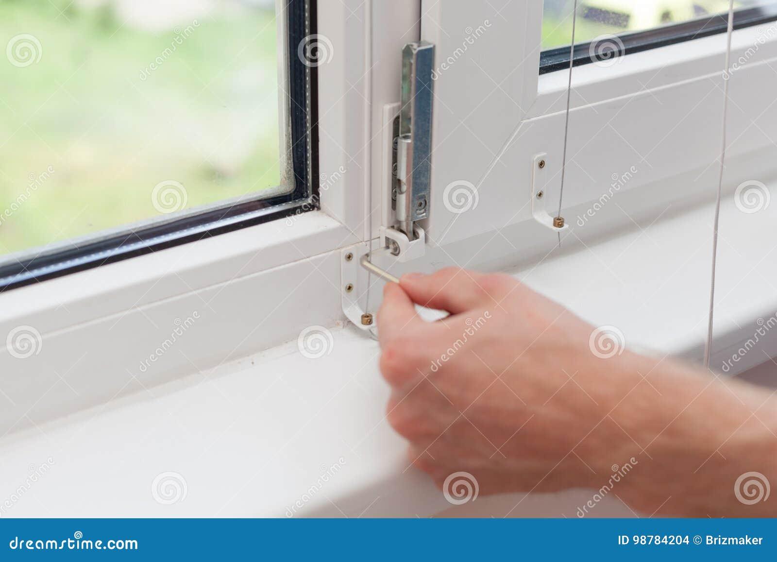 Het manusje van alles herstelt plastic venster met een zeshoek De werkman past de verrichting van het plastic venster aan