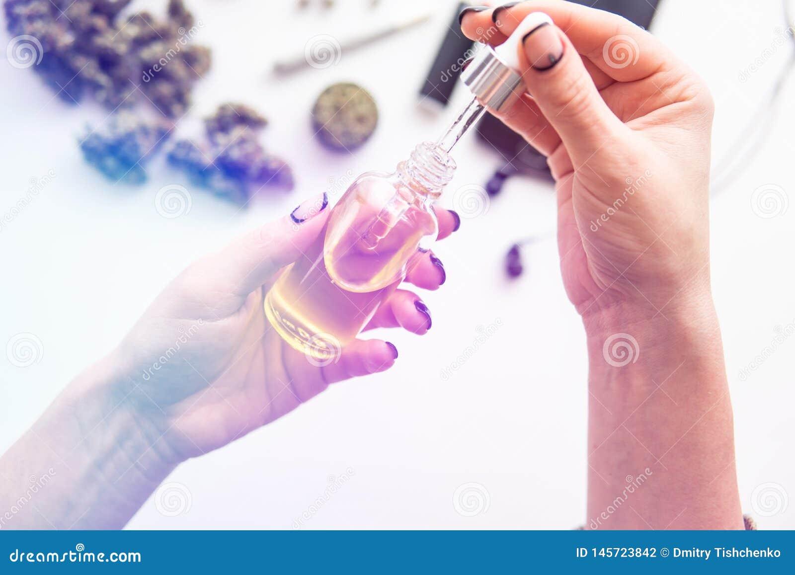 Het marihuanauittreksel op witte achtergrond, medisch hennepconcept, onkruidproduct, sluit omhoog, oliecannabis CBD in de hand va
