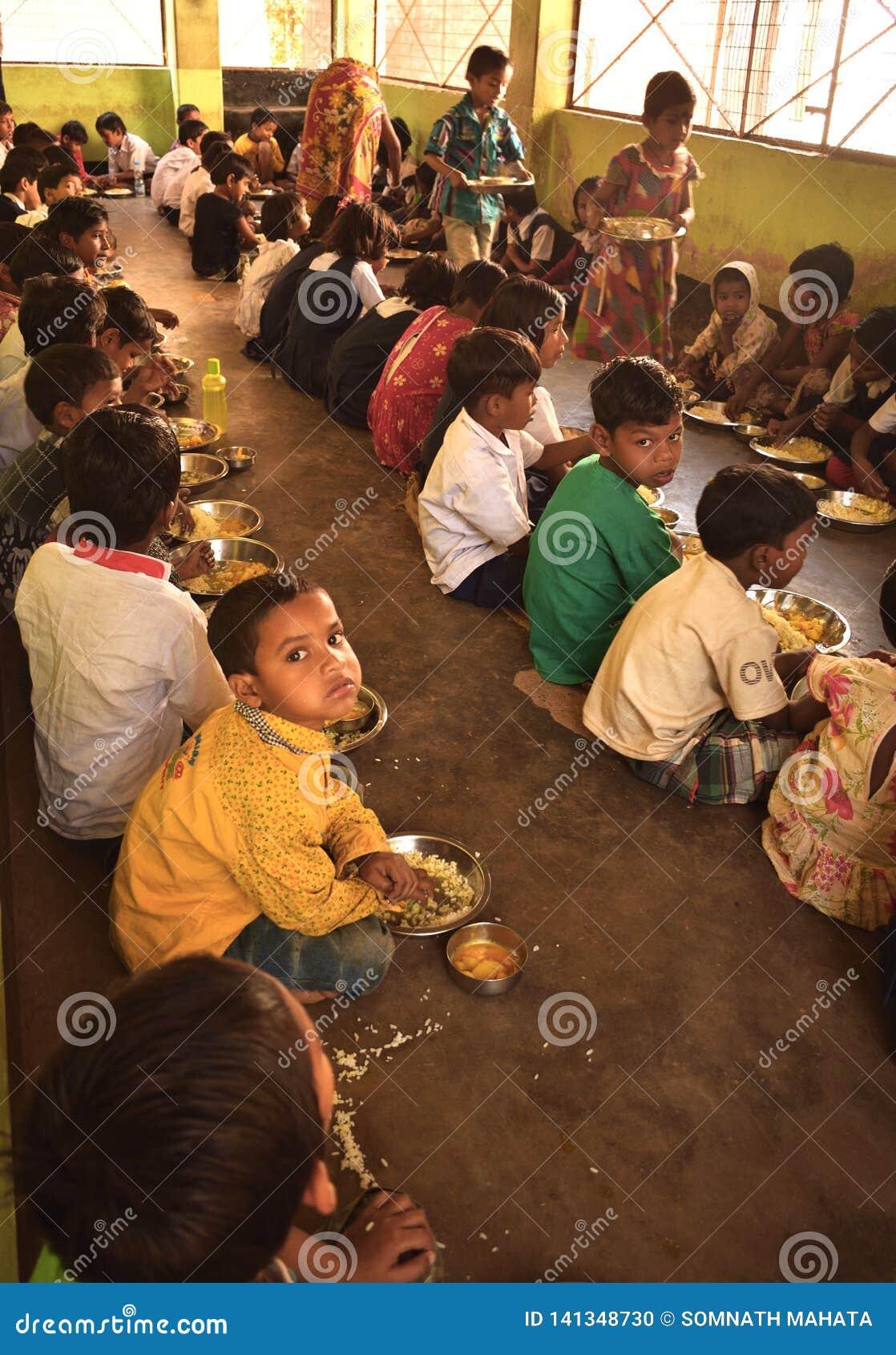 Het medio programma van de dagmaaltijd, een Indisch overheidsinitiatief, is lopend in een lage school De leerlingen nemen hun maa