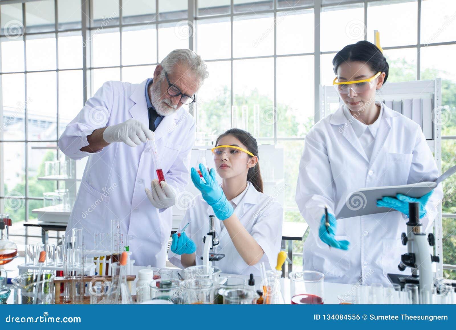 Het medische Onderzoek en de Wetenschappers werken met een microscoop en een tablet en Reageerbuizen, Micropipette en Analyseresu