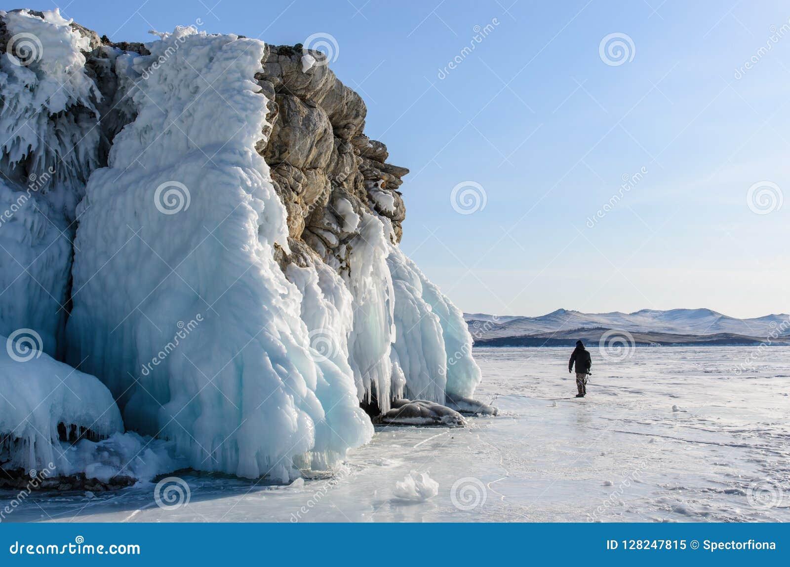 Het meer Baikal is behandeld met ijs en sneeuw, sterk koud, dik duidelijk blauw ijs De ijskegels hangen van de rotsen Het meer Ba