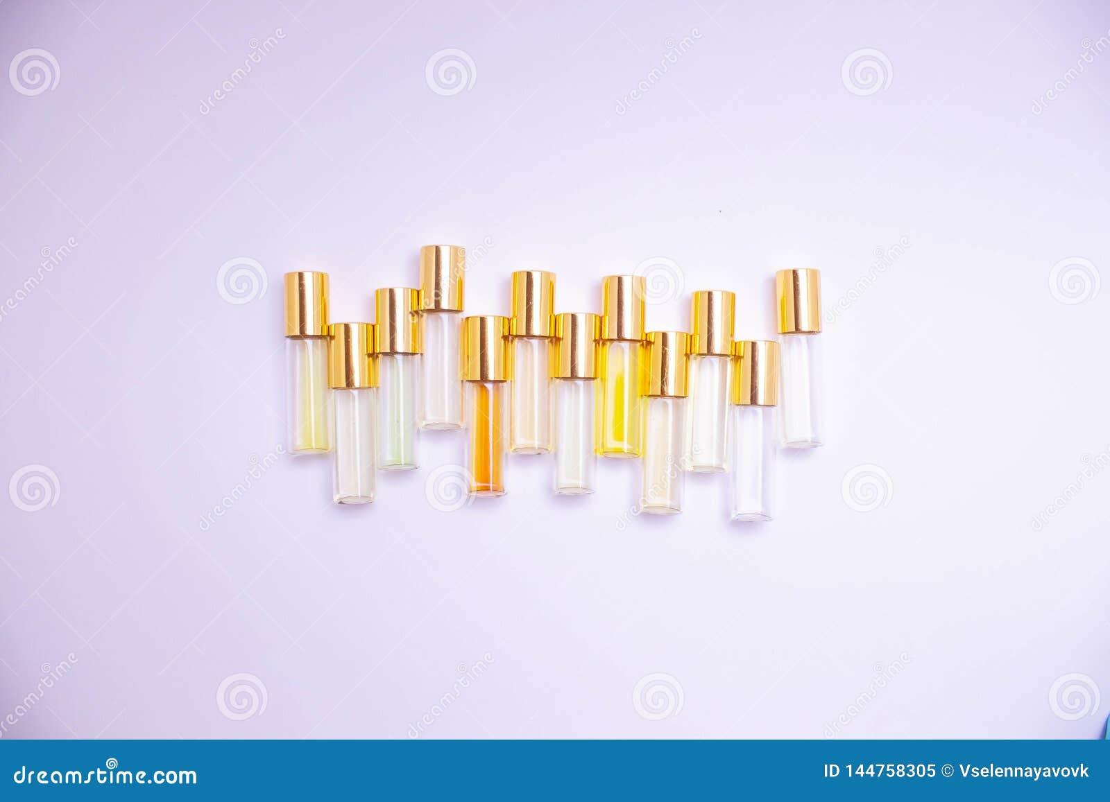 Het meetapparaatflesjes van het parfumglas van verschillende soorten op lichte achtergrond Parfumsteekproef
