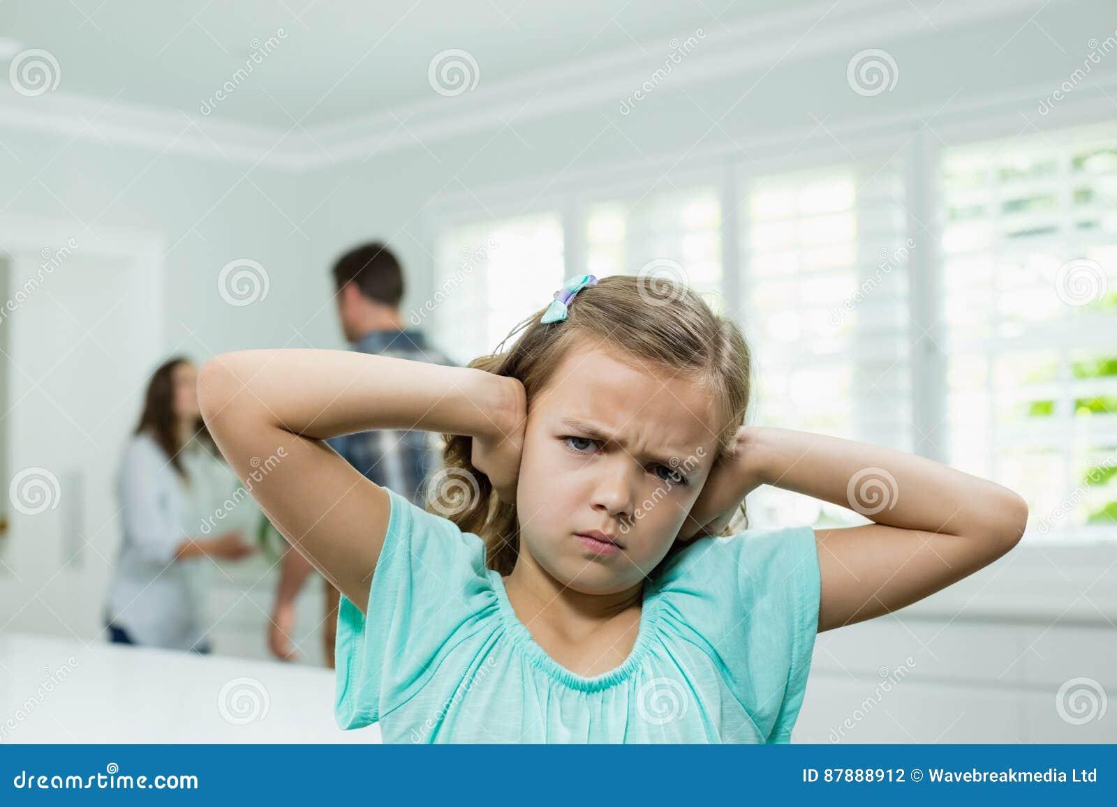 Het meisje behandelt haar oren met haar handen terwijl ouders die op achtergrond debatteren