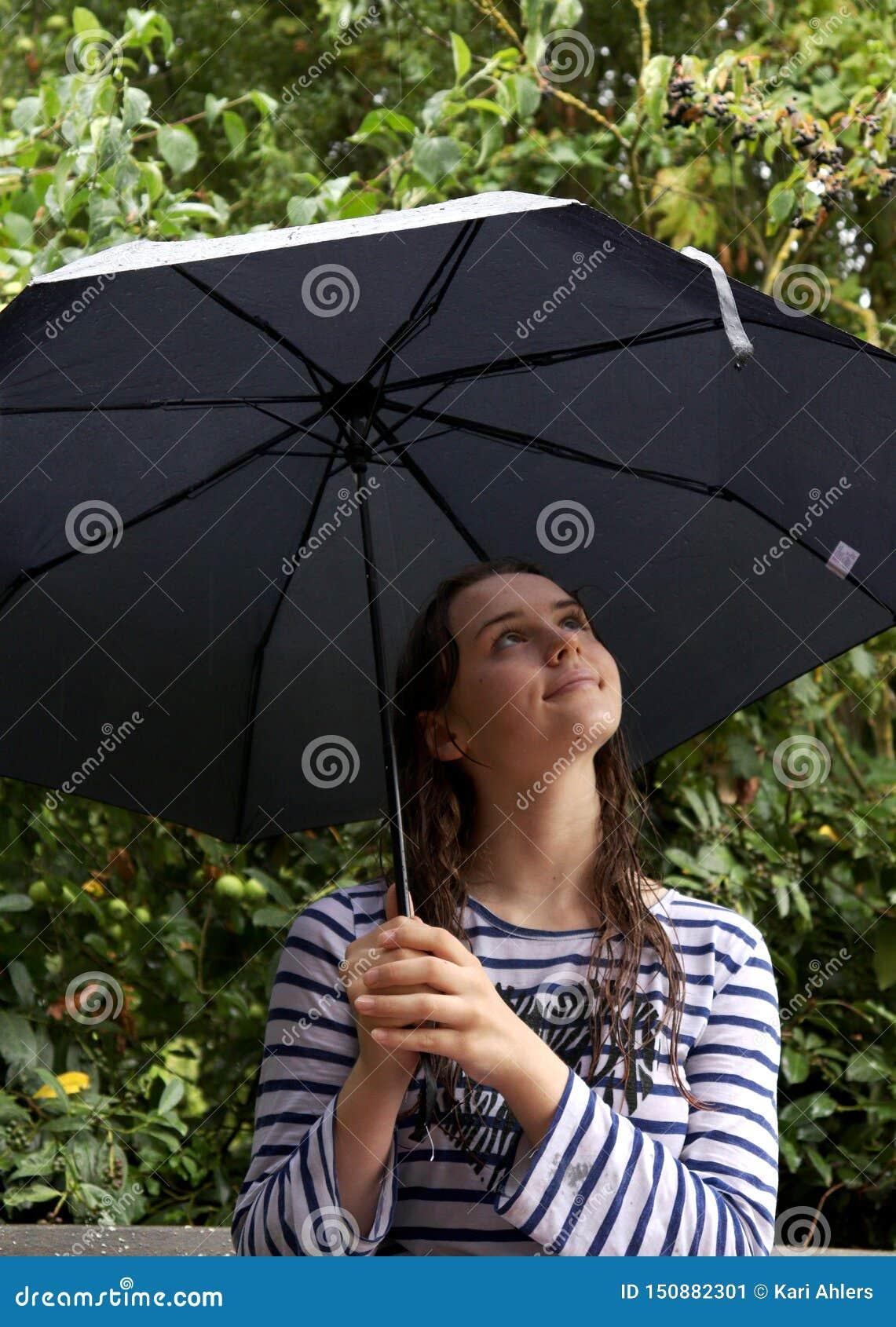 Het meisje bekijkt omhoog haar paraplu